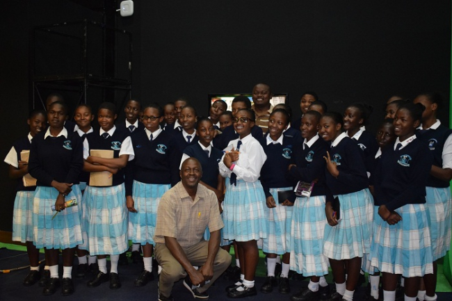Ali Manzu poses for a photo with the Nakuru Girls' High School in one of our studios.