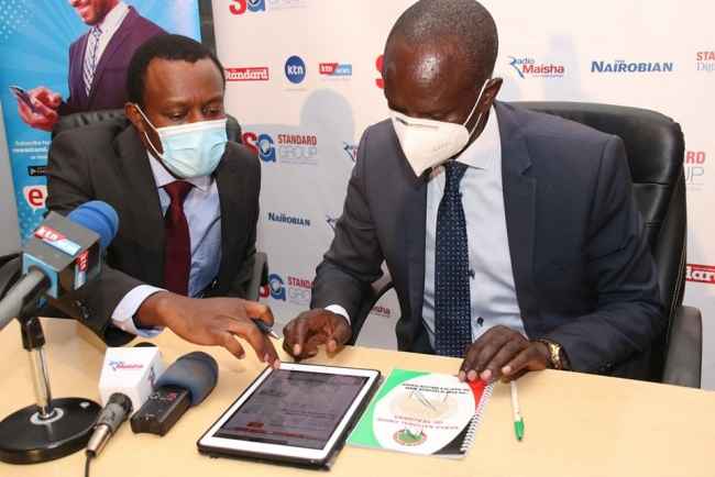 Orlando Lyomu  takes through KNUT Secretary General  Wilson Sossion(right)  the  standard E-papaer menus and features on an ipad