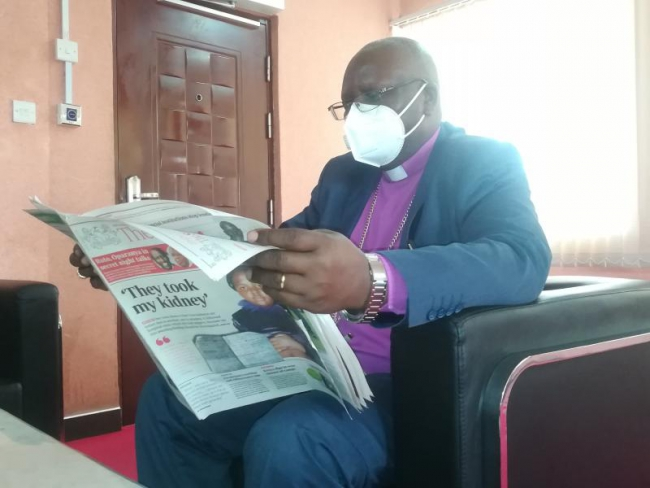 ABC Kenya Archbishop Timothy Ndambuki reads a copy of the newly re-launched Standard Newspaper at his office