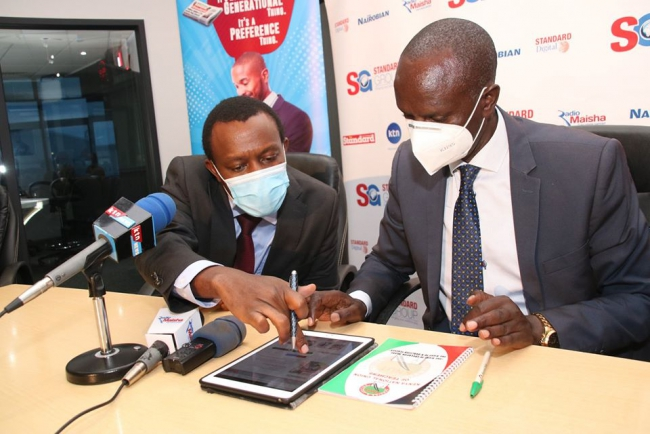 Standard Group CEO Orlando Lyomu  takes through KNUT Secretary General  Wilson Sossion(right)  the  standard E-papaer menus and features on an ipad