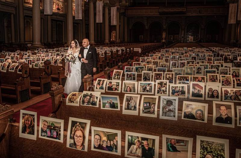 Bride walks aisle of empty church with photos on pews instead of wedding guests