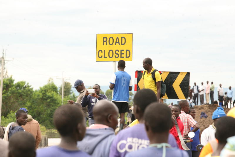 People mill around a signage at Ayweyo between Ahero and Katito in Kisumu County (Photo: Denish Ochieng)