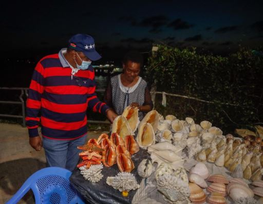 President Uhuru samples same of the wares displayed by a trader during his Mombasa tour (Photo: Courtesy)