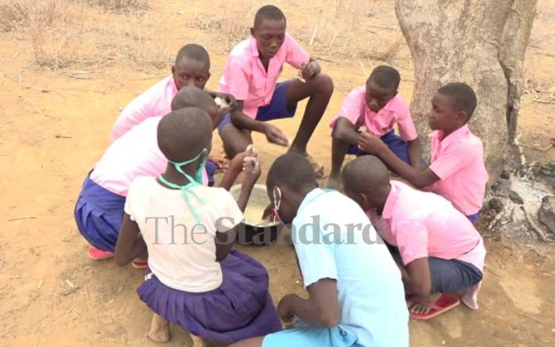 Ganze school where pupils sit on the floor, cook their own meals