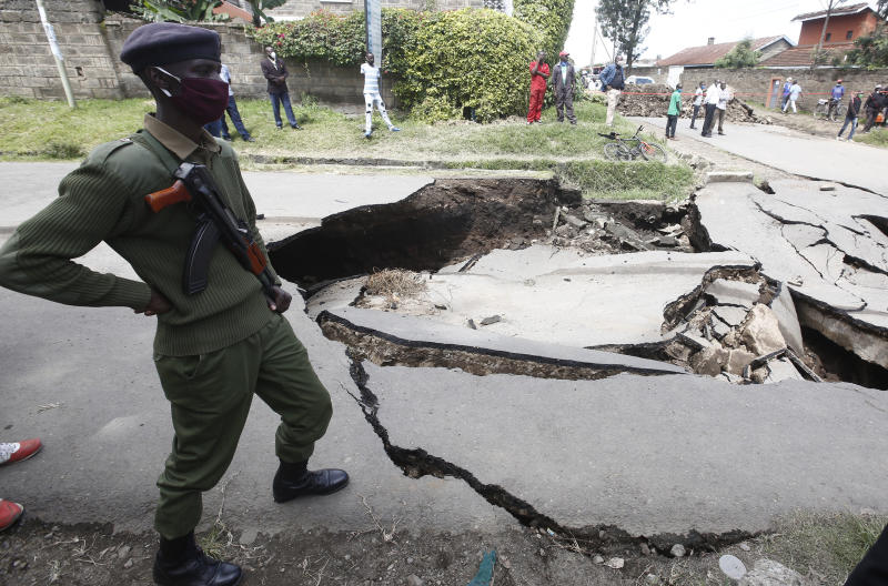 A police officer stands next to a collapsed section of John Momanyi road in Nakuru town. (Photo: Kipsang Joseph)