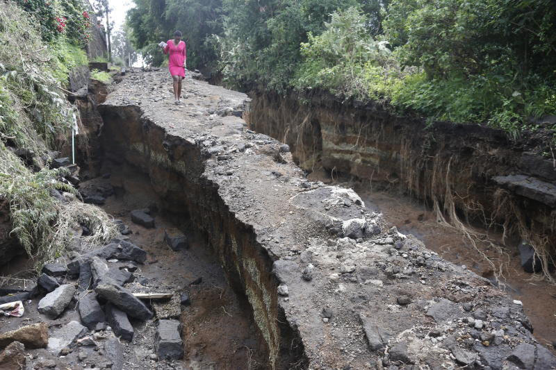 A woman crosses what remained of a road after a section of it collapsed (Photo: Joseph Kipsang)