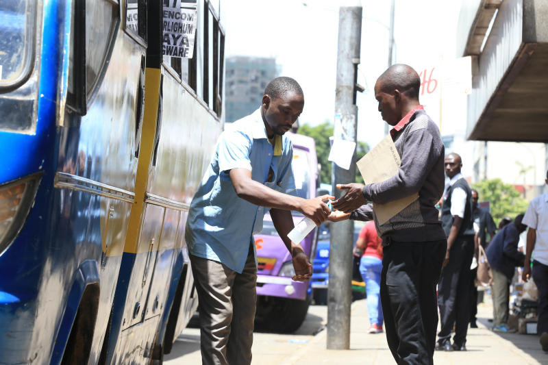 A customer sanitizes his hands before entering a bus at GPO in Nairobi (Photo: Stafford Ondego)