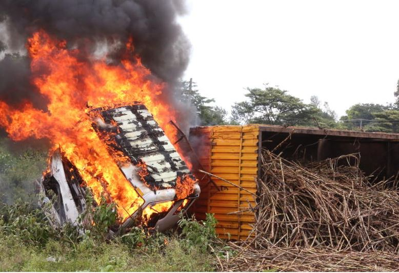 The wreckage of a sugarcane truck on fire after colliding with a matatu and a private car at Kisian junction in Kisumu County. Seven passengers were killed on the spot (Photo: Collins Oduor)