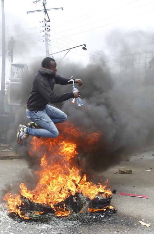 A demonstrator jumps over a bonfire lit by matatu operators during demonstrations in Nakuru Town (Photo: Kipsang Joseph, Standard)