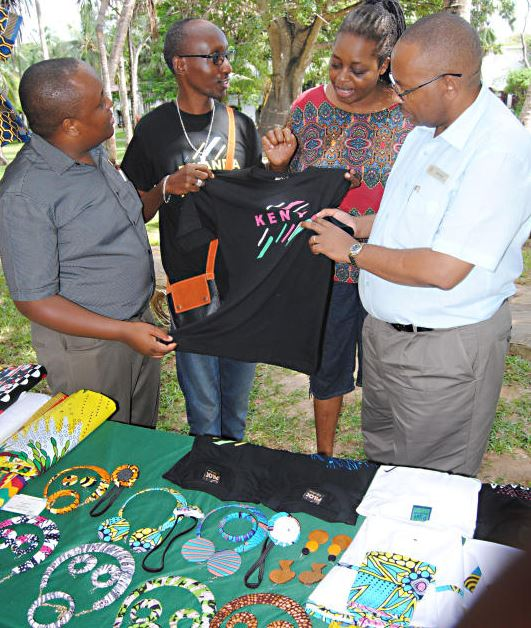 An artist from Rwanda,Ruyange Jose [2nd left] shows a T- Shirt to General Manager of' Serena Beach Resort and Spa in Mombasa, Herman Mwasaghua [right] during Mombasa Farmers and Artisans Market held at the Hotel.
