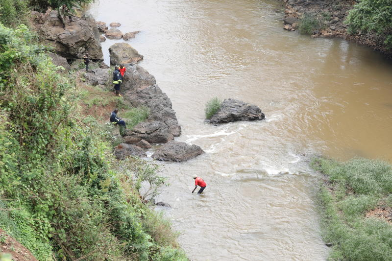 A man wades through River Muruguru in search of the body of a middle aged man who slipped and fell at the Muruguru falls in the outskirts of Nyeri town while taking a selfie in the company of his girl