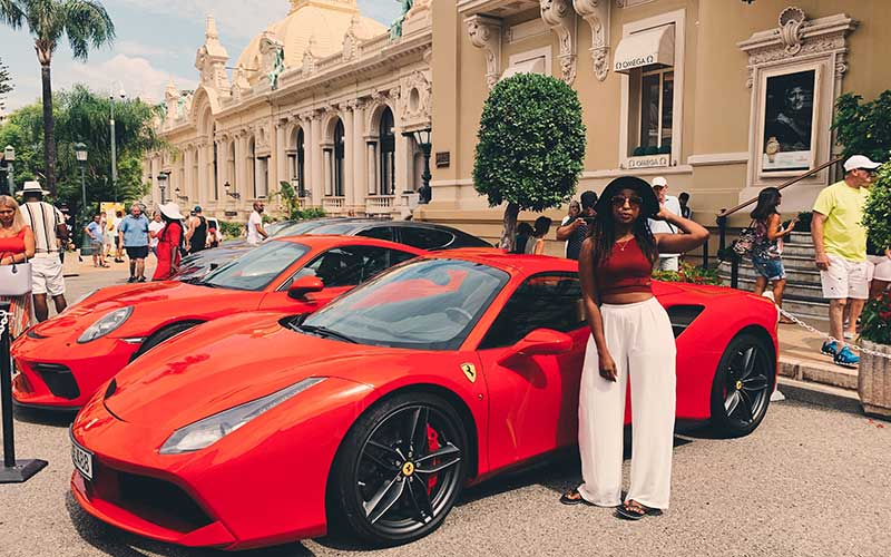 Natalie Tewa poses beside luxury automobiles in one of her international travels. [Courtesy]