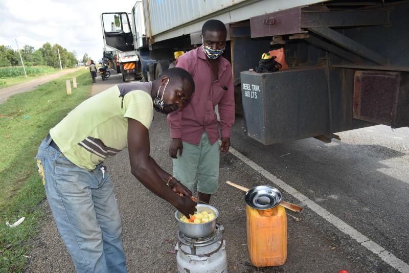 George Paluk (left) and Silas Baya prepare a meal at Busia waiting for the Kenya-Uganda border to be reopened. (Photo: Mumo Munuve)