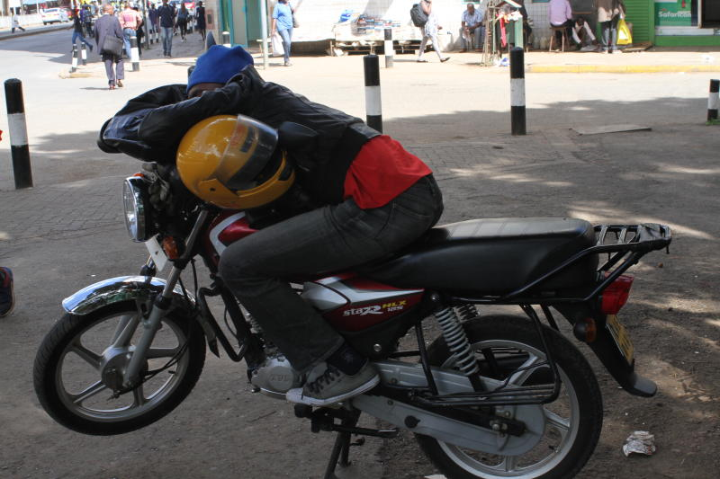 A Boda boda operator relaxes on top of his bike along Moi Avenue in Nairobi. Many businesses in the city have been affected following government's order to have people stay at home. (Photo: Collins Kw