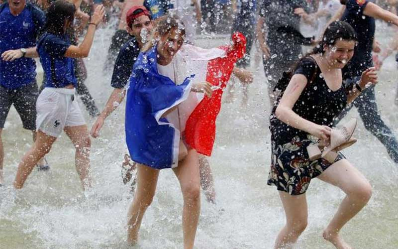 France fans react in a fountain after they defeate