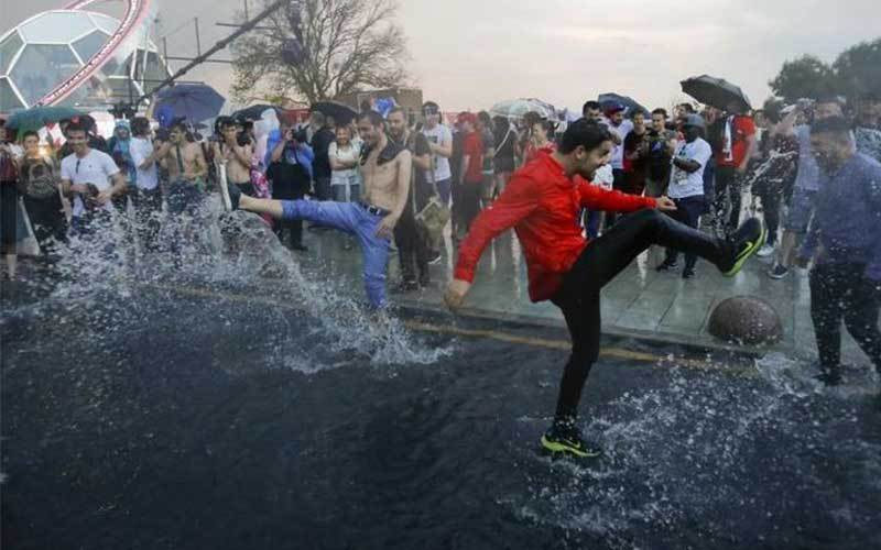 Fans play in a puddle after heavy rain following t