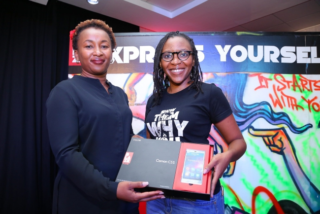 Safaricom Director of Consumer Business Unit, Sylvia Mulinge (L) and Safaricom Senior Manager Youth Segment, Marion Njeri unpack the BLAZE enabled starter phone kit during the launch of Safaricom's ne