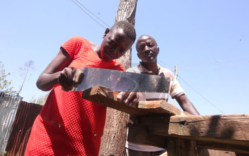 High school student gains carpentry skills from father's workshop