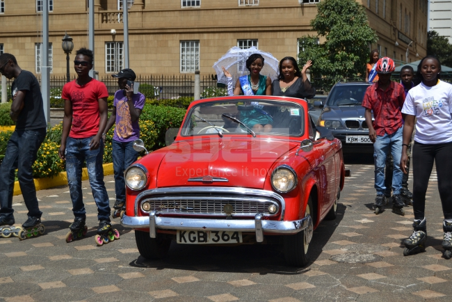 Nairobi contestant arrives in a vintage car, being escorted by skaters