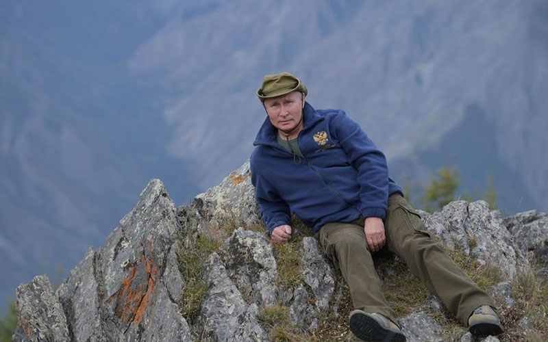 Vladimir Putin poses on rocky hilltop as he celebrates 67th birthday in forest